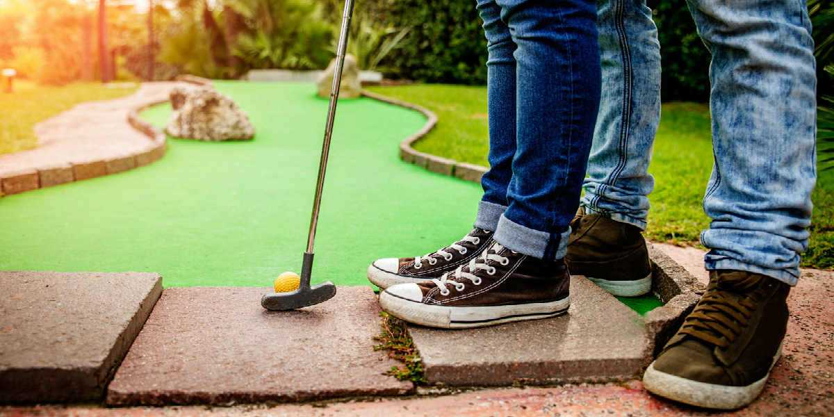 adult and child playing mini-golf