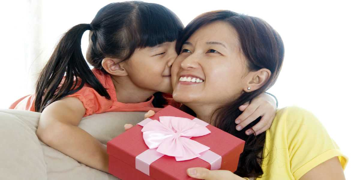 girl giving her mother a kiss and a present