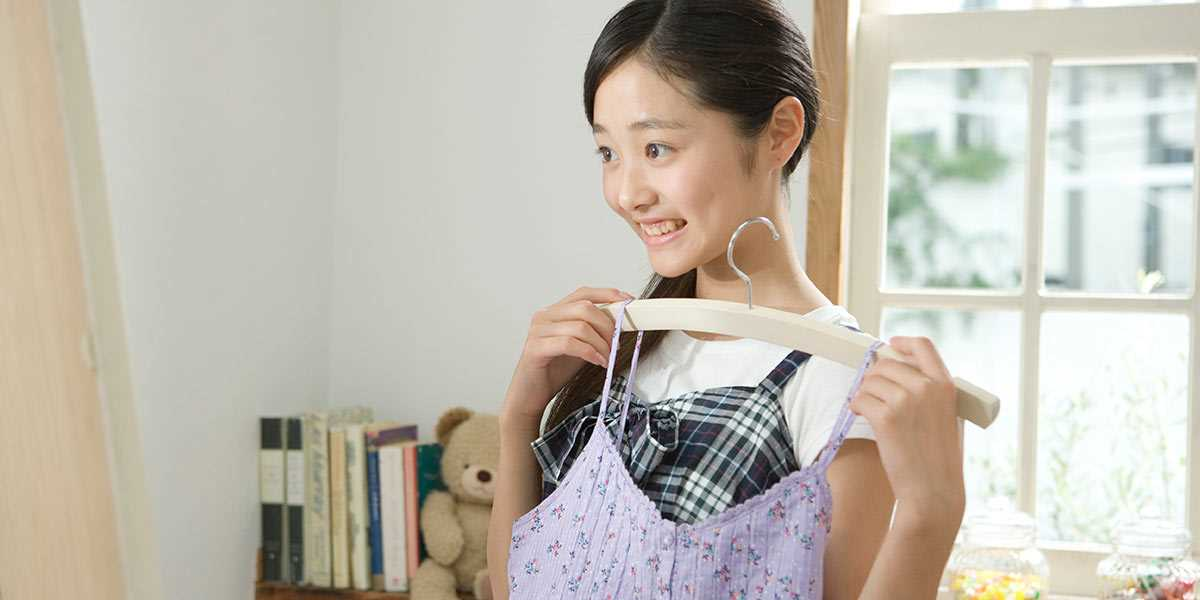 A teenage girl looking at a mirror holding a dress