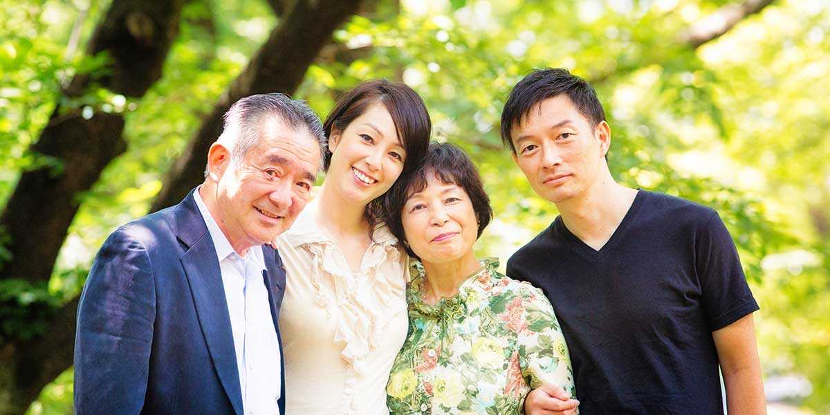 An elderly couple and a young couple posing for a photo