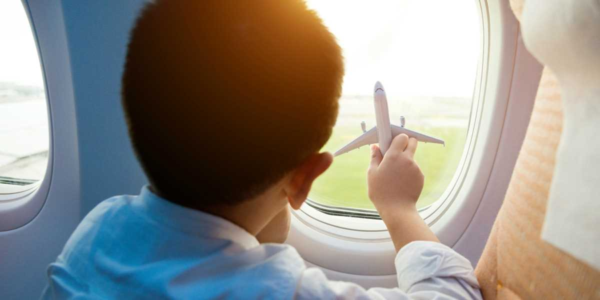 A boy holding an aeroplane model against the aeroplane window