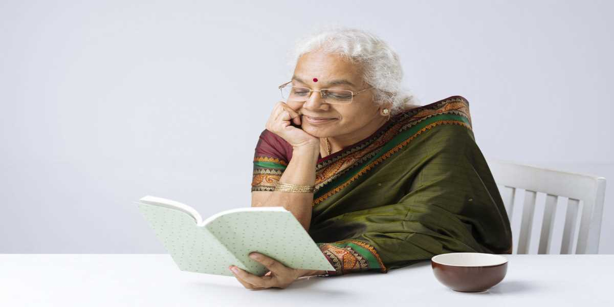 An elderly Indian lady reading a book