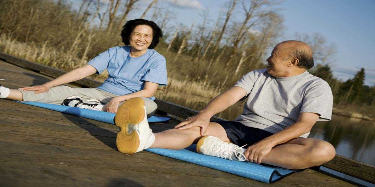 An elderly Asian couple doing stretching exercises