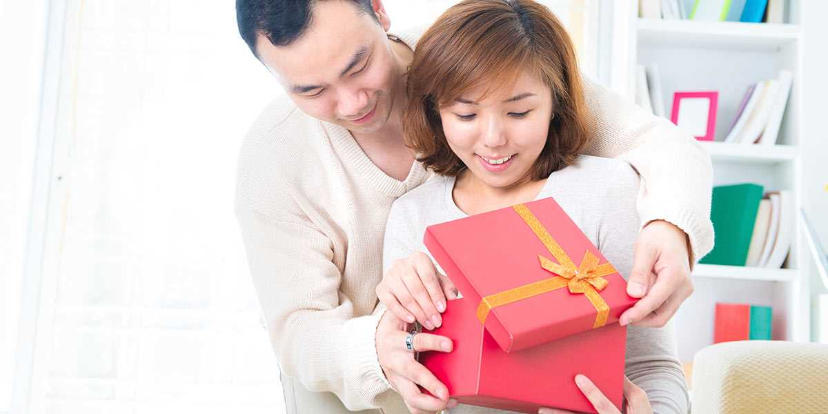 A husband surprising his wife with a gift box