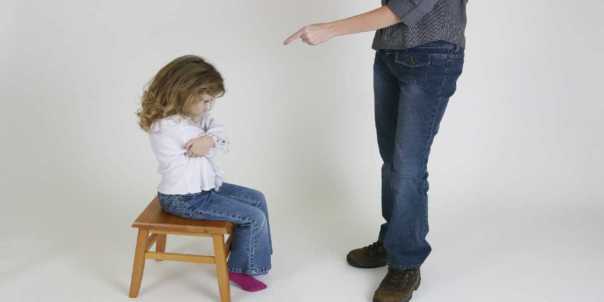 A little girl being scolded while seated down