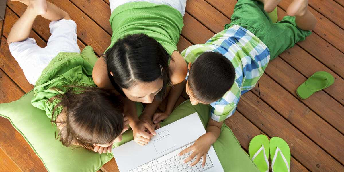 A mother and two children looking at a laptop