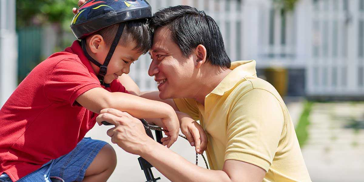 A father encouraging his son in cycling
