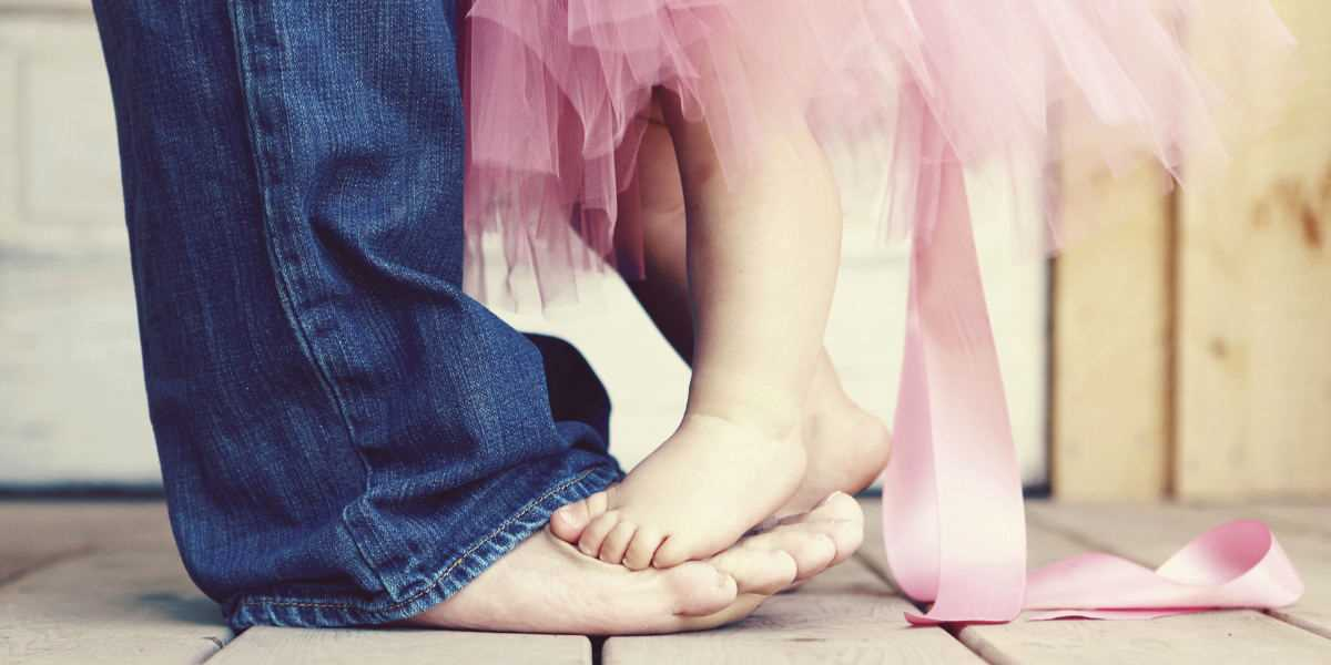 A little girl stepping on her father's feet