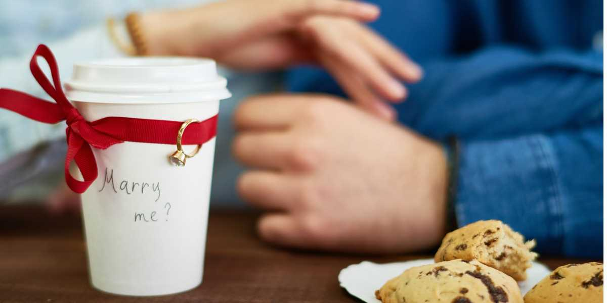 A marriage proposal on a coffee cup with a ring tied to it