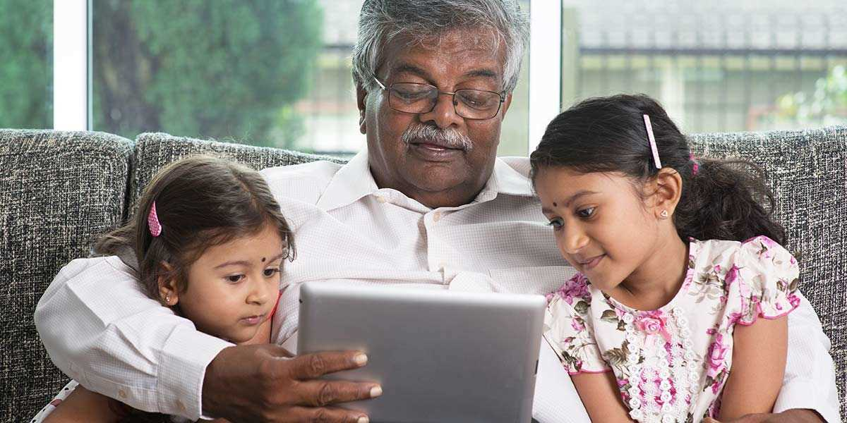 A grandfather with two granddaughters looking at a tablet devide