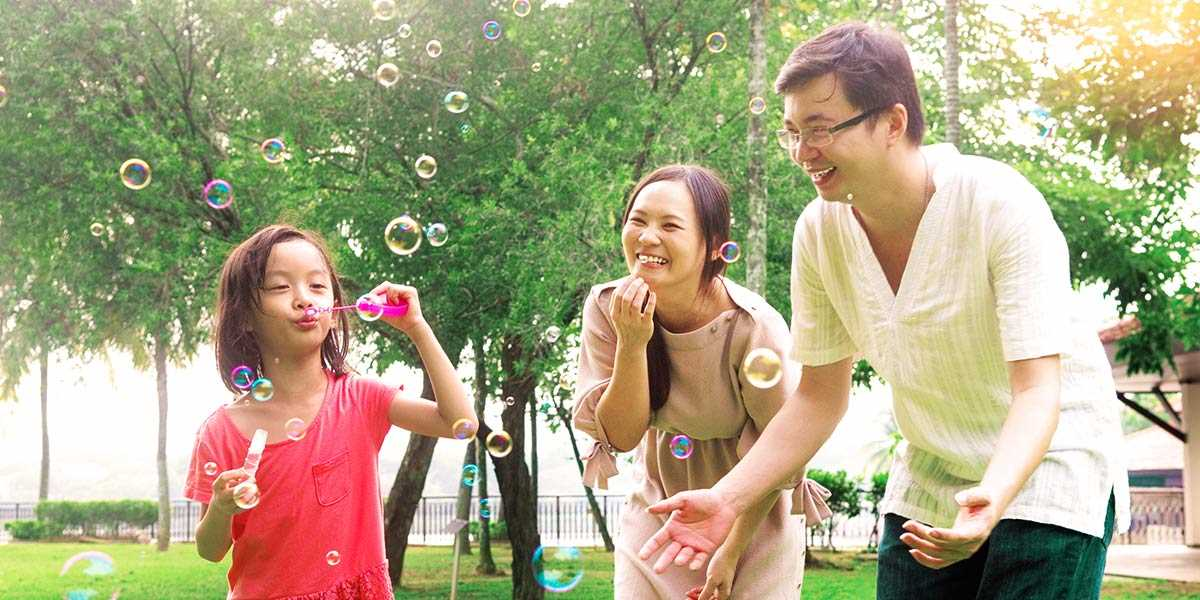A happy family of three blowing bubbles in a park