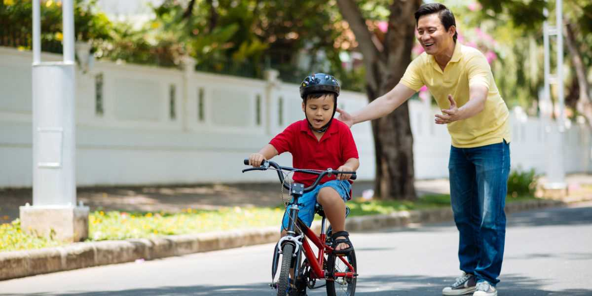 A father teachiing his son to cycle