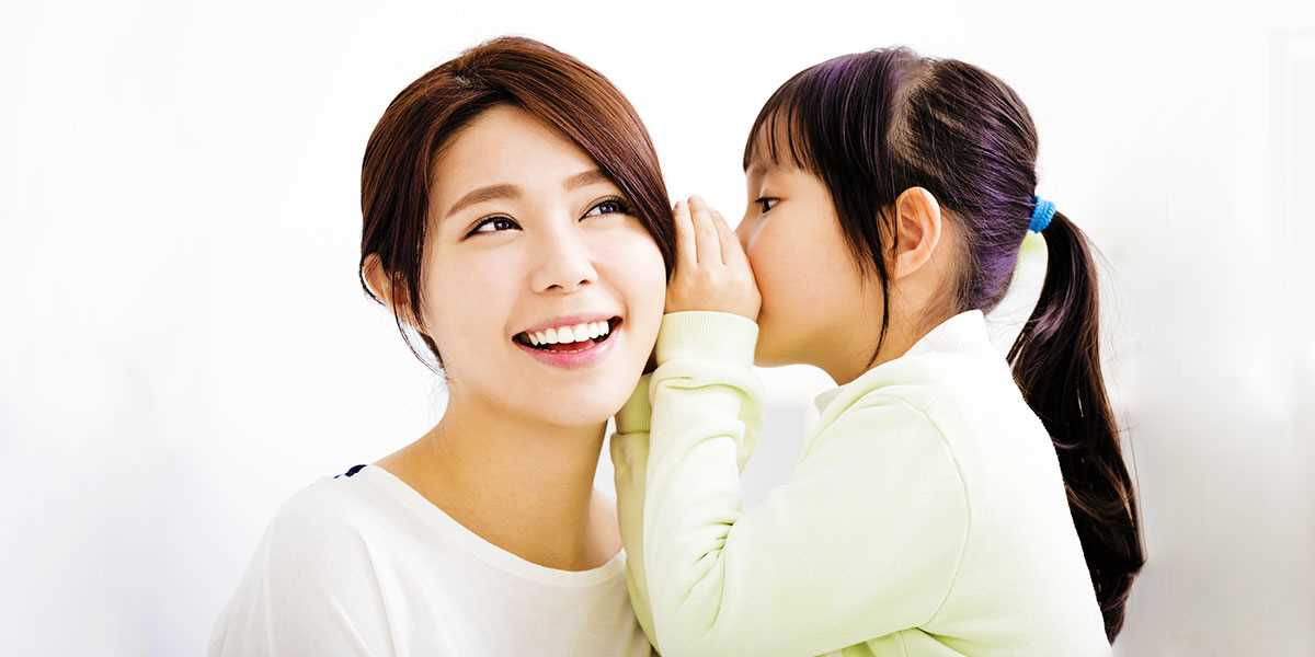 A daughter whisepering into her mother's ear
