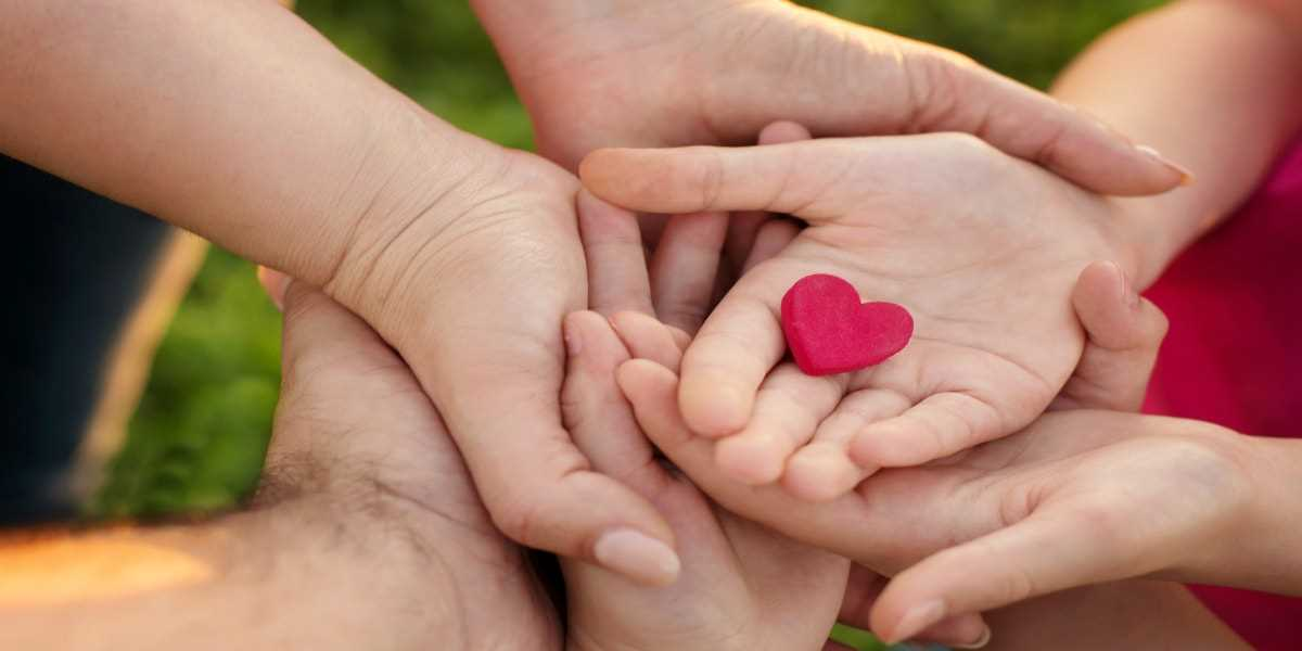 Family hands stacked on top of each other holding a small red heart