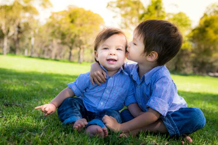 An elder brother giving his baby brother a kiss on the cheek