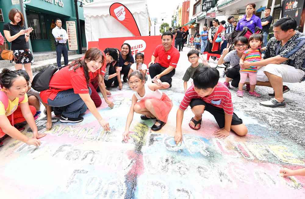 "Minister for Social and Family Development Desmond Lee and Families For Life Council members joined children and their families in a chalk doodling activity at Circular Road for Families for Life's ""My Family Weekend Fun Day"" on 2 Sep 2018"