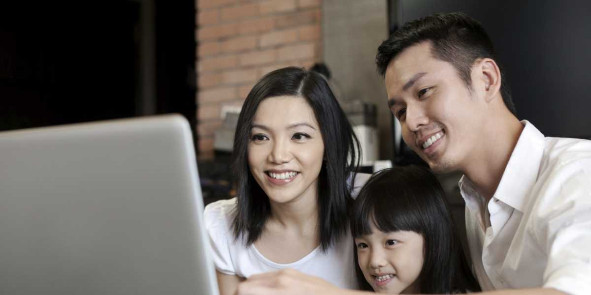 A family of three looking at a computer screen