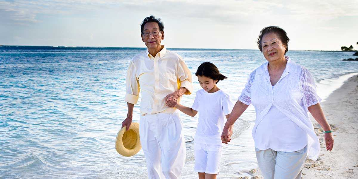 Grandparents strolling on the beach with their grandchild