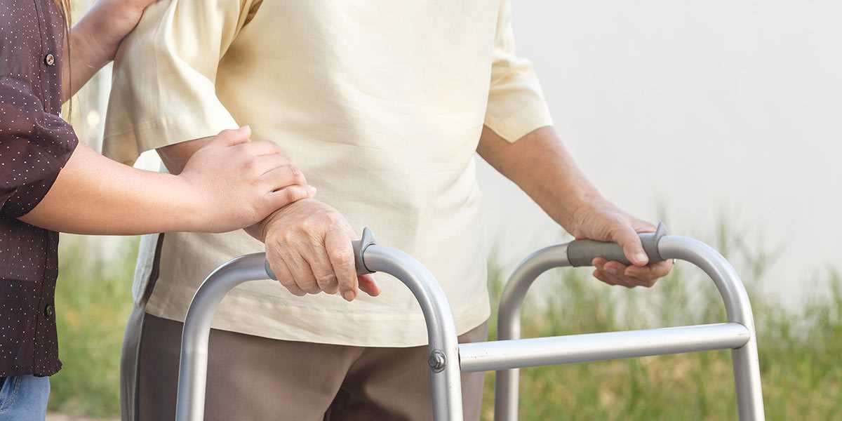 Supporting an elderly lady on a  assisted walker