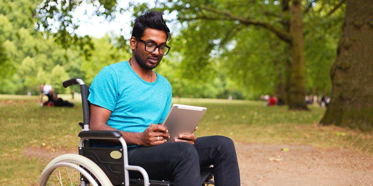 A man in a wheelchair looking at a tablet