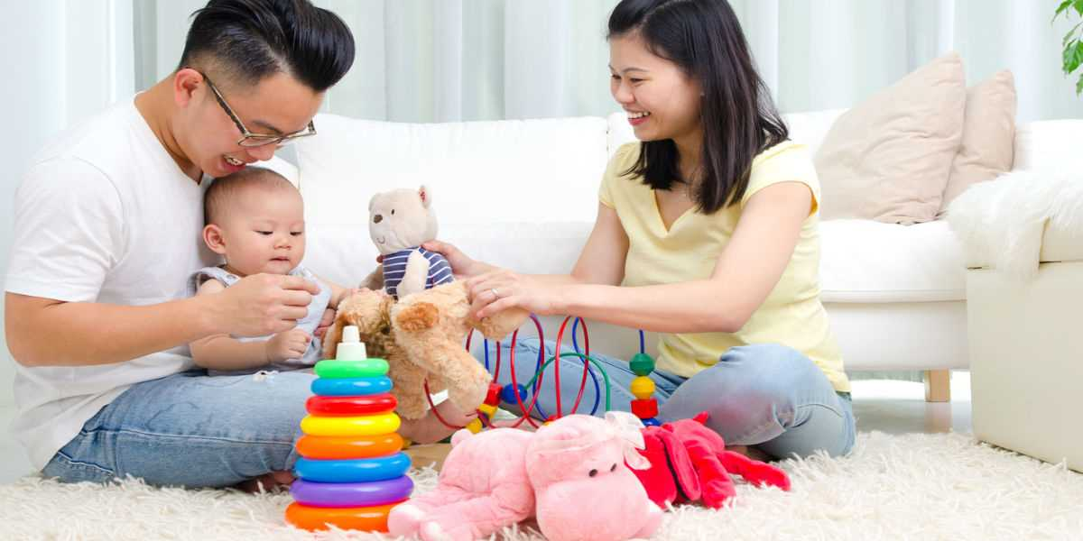 Young parents playing toys with their baby