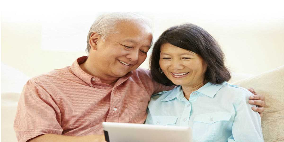 An elderly Asian couple looking at an electronic tablet