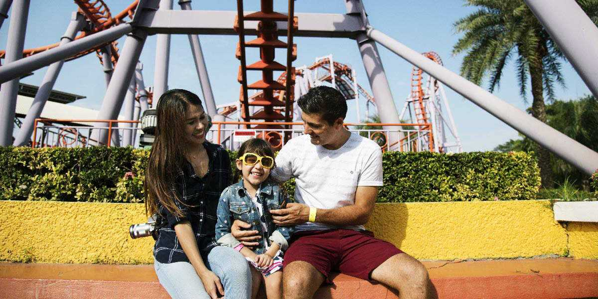 Happy parents and daughter at a themepark