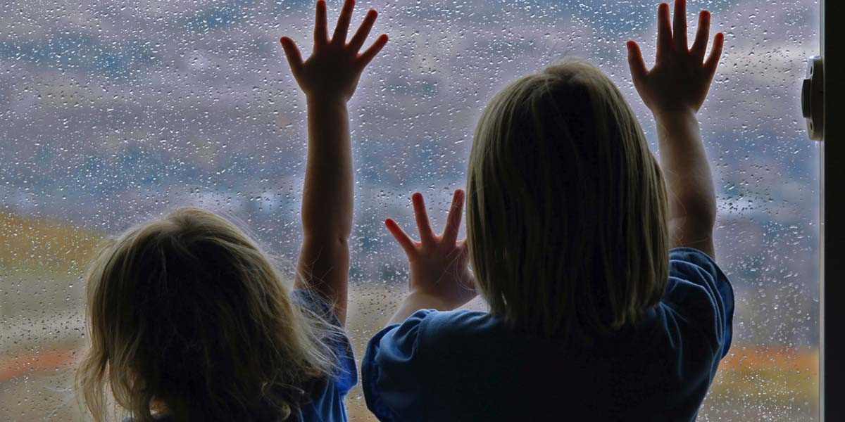 girls looking out at the rain through a window